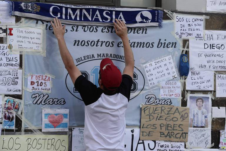 Homem coloca cachecol escrito Gimnasia em mural com mensagens para Maradona