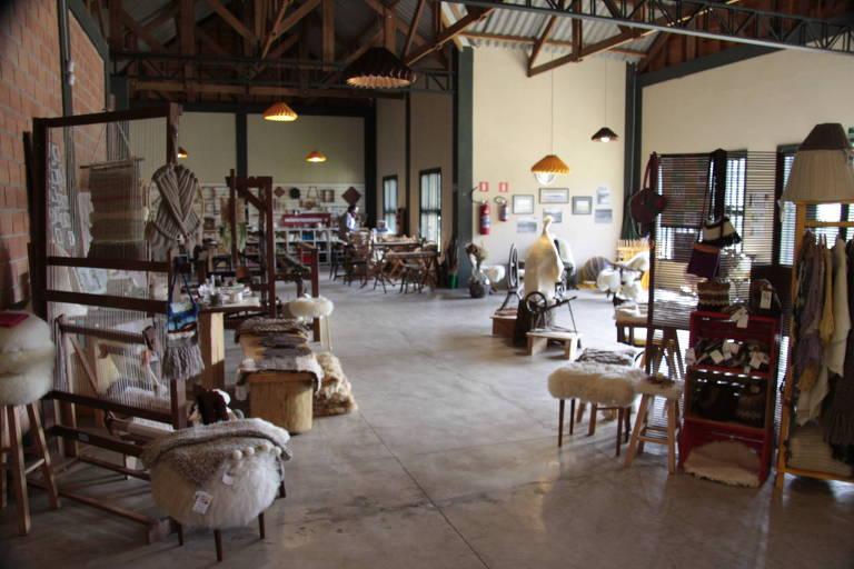 galpão com peças de lã sendo vendidas em cima de móveis de madeira