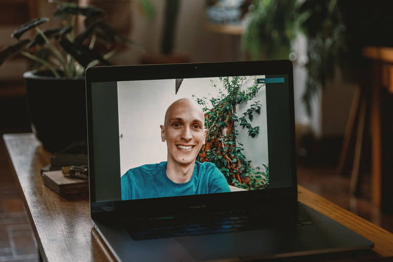 Vemos um jovem bem magro, com a cabeça raspada, sorridente, tendo ao fundo uma parede branca com plantas; ele está enquadrado por um laptop, pois a foto foi feita a distância a partir da casa do fotógrafo