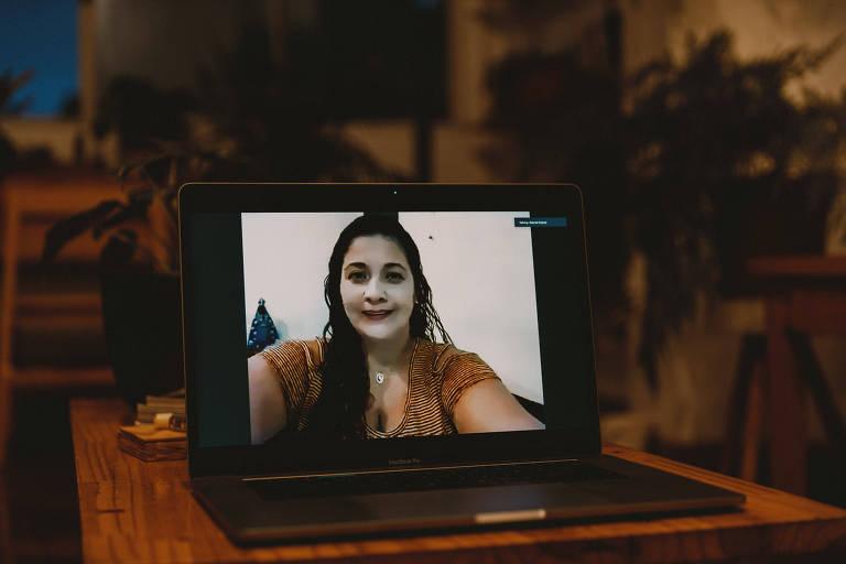 Carla Brito, 41, descobriu que tinha câncer de colo de útero somente após fazer uma histerectomia; seu diagnóstico demorou quase um ano; Lei dos 30 Dias busca evitar casos assim. É uma moça bem clara, com cabelos compridos, cheinha e sorridente, que vemos enquadrada em um laptop, pois a foto foi feita a distância, a partir da casa do fotógrafo