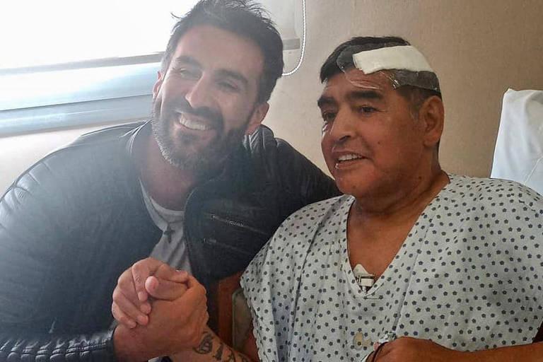 Maradona ao lado do médico Leopoldo Luque após receber alta em hospital de Buenos Aires, na Argentina