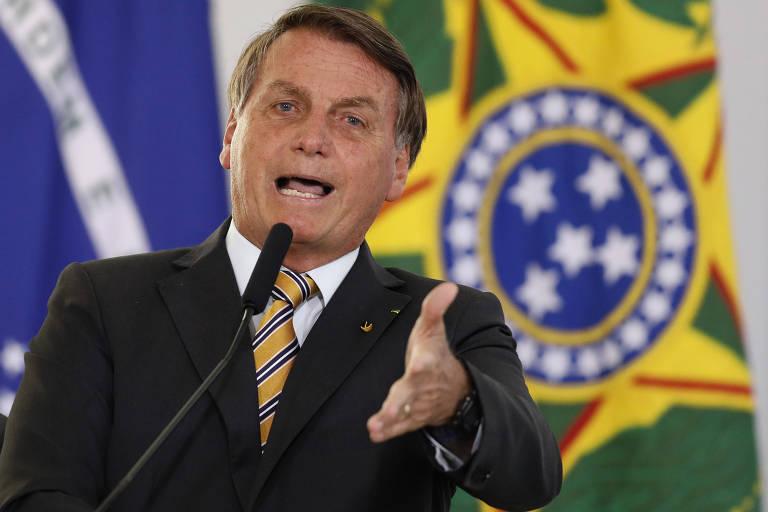 Bolsonaro fala em microfone com bandeiras do Brasil ao fundo