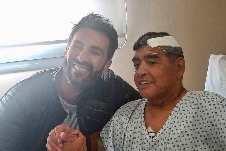 O ex-jogador Diego Maradona, que passou por intervenção cirúrgica na cabeça, ao lado de seu médico Leopoldo Luque, após receber alta