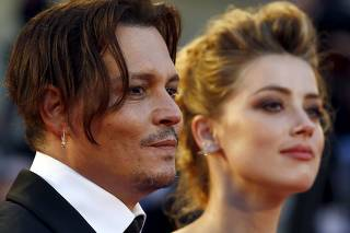 FILE PHOTO: Actress Amber Heard and her husband Johnny Depp attend the red carpet event for the movie
