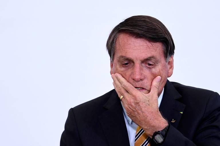 Bolsonaro passa a mão esquerda com força abaixo do olhos, puxando a pele da região e aumentando a abertura dos olhos
