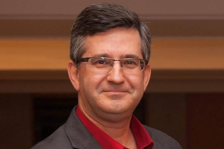 Homem de 57 anos, grisalho, de óculos, sorri para foto