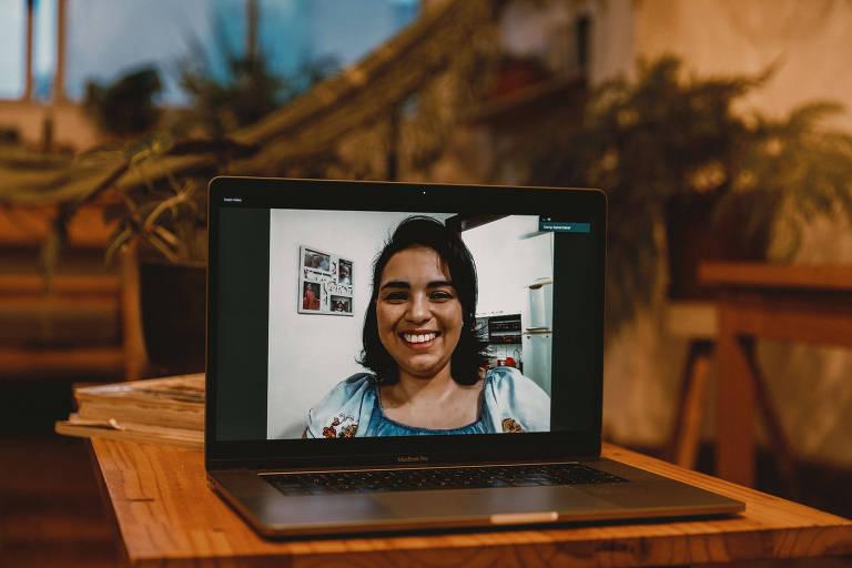 A designer de interiores Vivam Mota, 40, descobriu câncer durante a gestação; Viviam, morena e sorridente, tem os cabelos lisos e castanhos na altura dos ombros e aparece enquadrada em close na tela de um laptop, pois a foto foi feita a distância, a partir da casa do fotógrafo