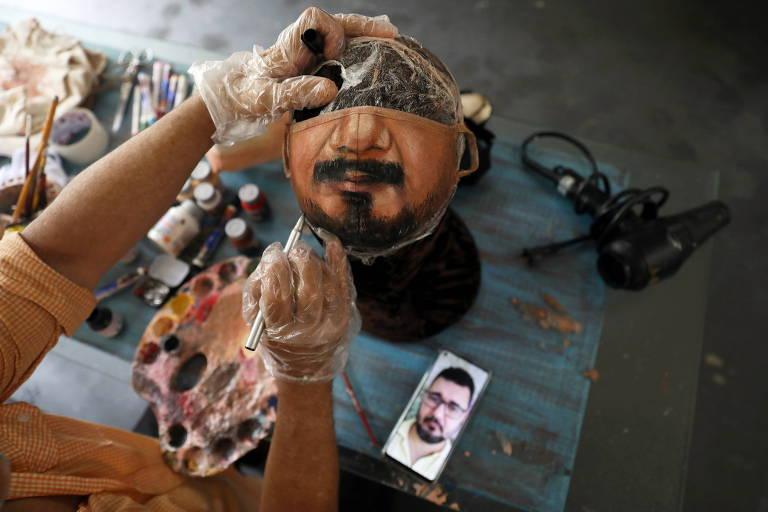 O artista plástico Jorge Silva Roriz pinta uma máscara protetora customizada olhando a foto de um homem em seu celular.