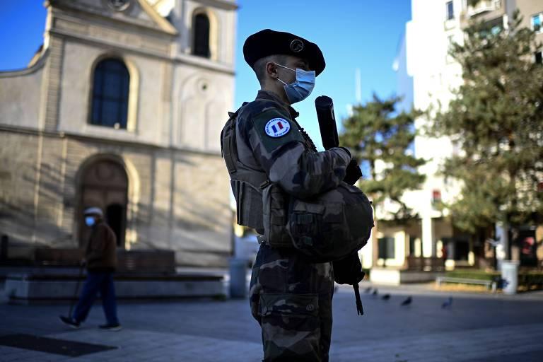 Soldados franceses durante patrulha próxima a igreja nos subúrbios de Paris