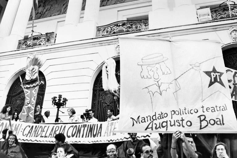 Pessoas erguem cartazes e faixas em frente à prédio