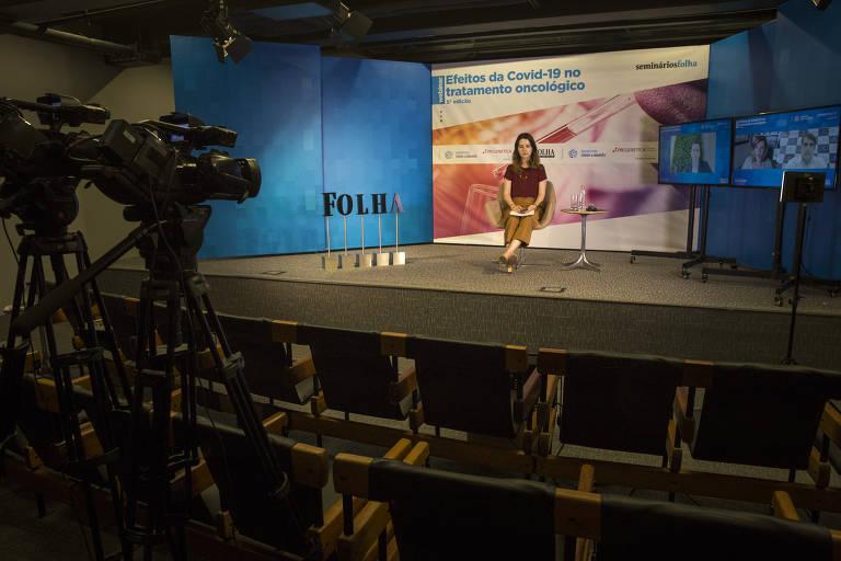 Foto mostra câmera filmando palco onde está a jornalista Mariana Versolato