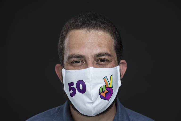 Guilherme Boulos posa com máscara branca com seu número de candidato escrito em roxo, em fundo preto.