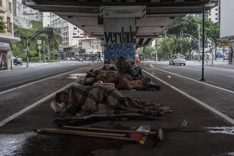 Pessoas em situação de rua estão deitadas umas do lado das outras no chão, com cobertores, em baixo de um elevado.