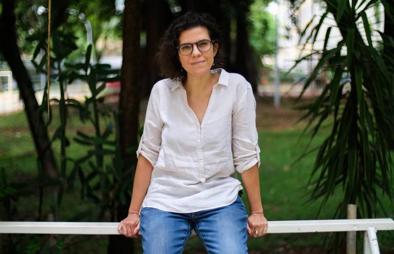 Professora Flávia Biroli, de pé, apoiada em cerca