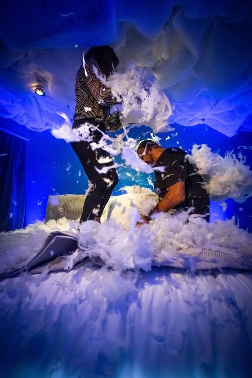 Casal faz guerra de travesseiro em quarto de funda azul