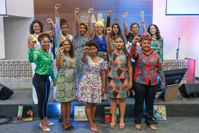 Grupo de doze mulheres negras, vestem roupas sociais coloridas e estampadas, parte usa turbante, estão com punhos levantados, ao fundo símbolo da OAB