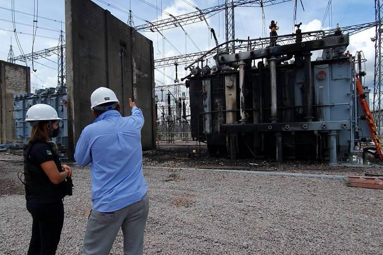 Duas pessoas observam um transformador queimado