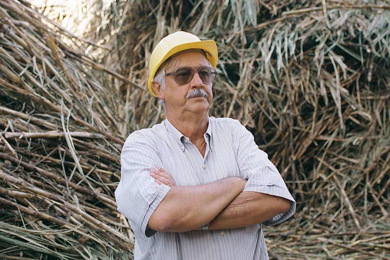 Um senhor de braços cruzados; ao fundo, ripas de cana-de-açúcar