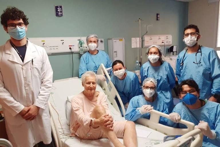 Vemos um senhor de cabelos brancos, sentado de bata hospitalar num leito, cercado por sete profissionais da área médica, seis deles de roupas azuis, do lado direito da foto, e um, de jaleco branco, do lado esquerdo