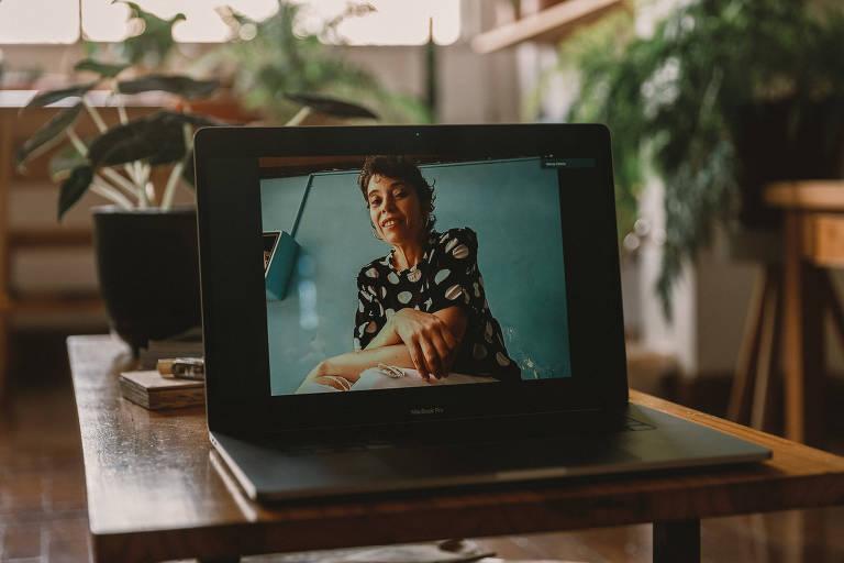Vemos uma mulher de cabelos curtos, calça branca e blusa estampada, sentada contra um fundo verde-azulado; ela está enquadrada em um laptop, pois a foto foi feita a distância a partir da casa do fotógrafo