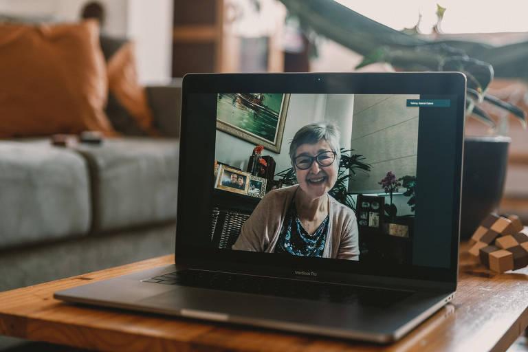 Vemos uma senhora de cabelos grisalhos curtinhos, de óculos, sorridente; ela é fotografada enquadrada na tela de um laptop, pois as imagens foram feitas a distância, a partir da casa do fotógrafo