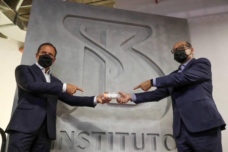 Joao Doria, governador de São Paulo, e Dimas Covas, diretor do Butantan, mantêm distância ao segurar caixa de Coronavac com a mão esquerda em evento para a imprensa no instituto, na capital paulista. Eles estão na frente de um grande B, que é o símbolo do Instituto Butantan
