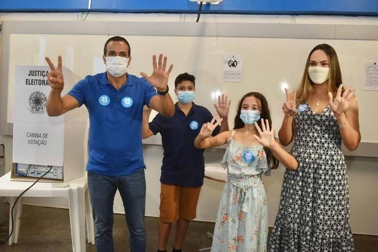 Casal e duas crianças fazem sinal de 25 com as mãos ao lado de urna eletrônica