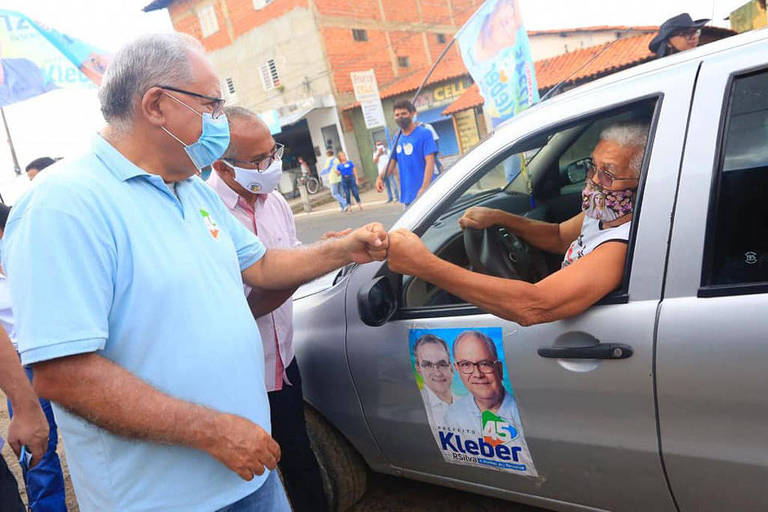 Homem idoso com camisa azul cumprimenta outro idoso que está dentro de carro