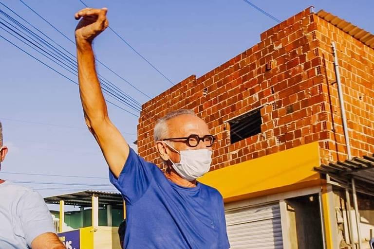 Homem idoso com camiseta azul, de máscara e óculos, com o braço pra cima