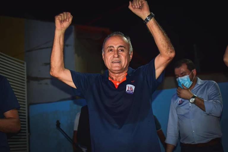 Homem de camisa azul escuro com braços para alto comemora.