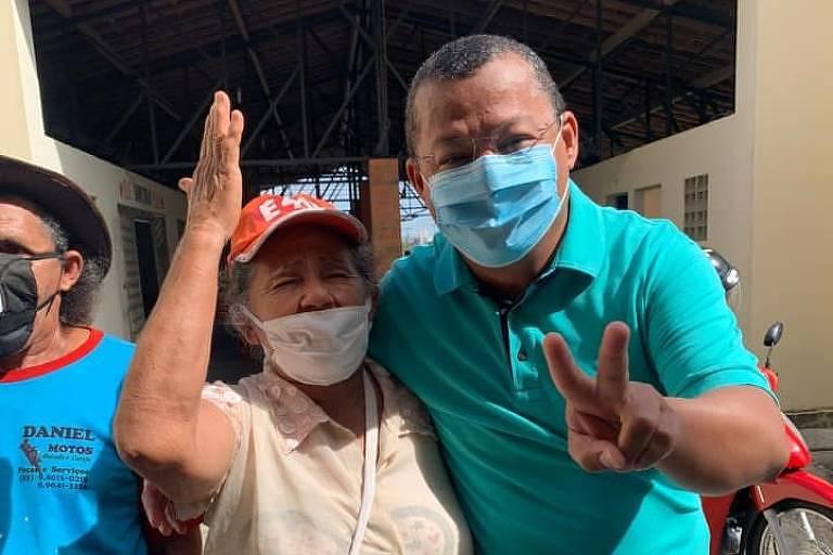 Homem de azul, com máscara, posa para foto com senhora