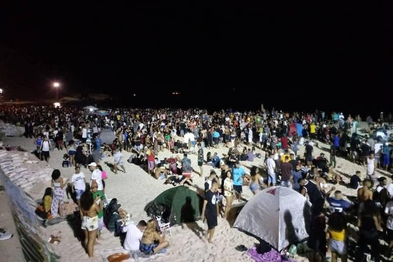 Muitas pessoas na praia, à noite.