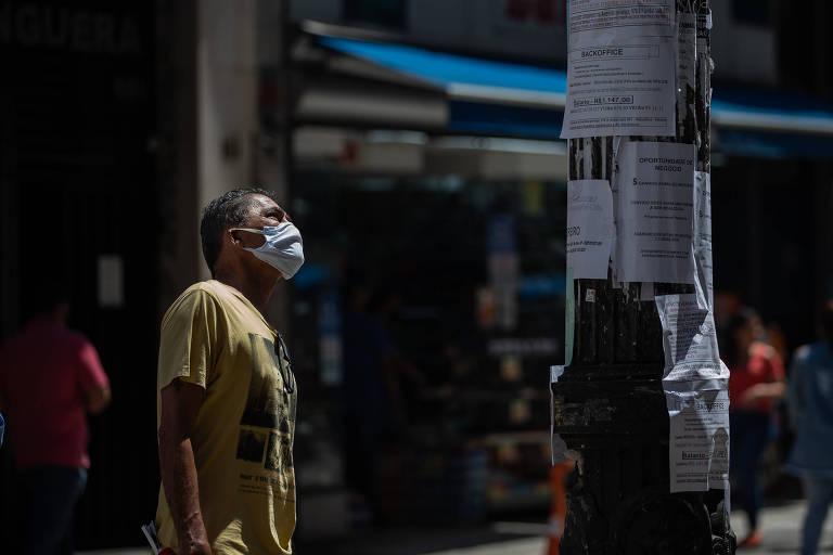 Homem olha anúncios de vagas de empregos no centro de São Paulo