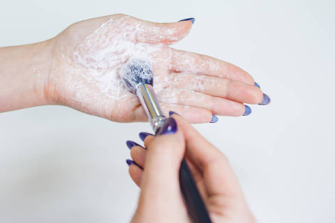 Hygienic care of makeup artist tools, women's hands wash the brush from cosmetics, soap and cleaning products, white background