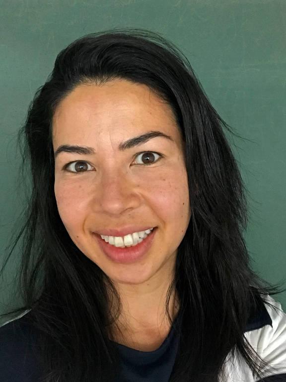 Mulher asiática de cabelos pretos sorri com lousa verde ao fundo