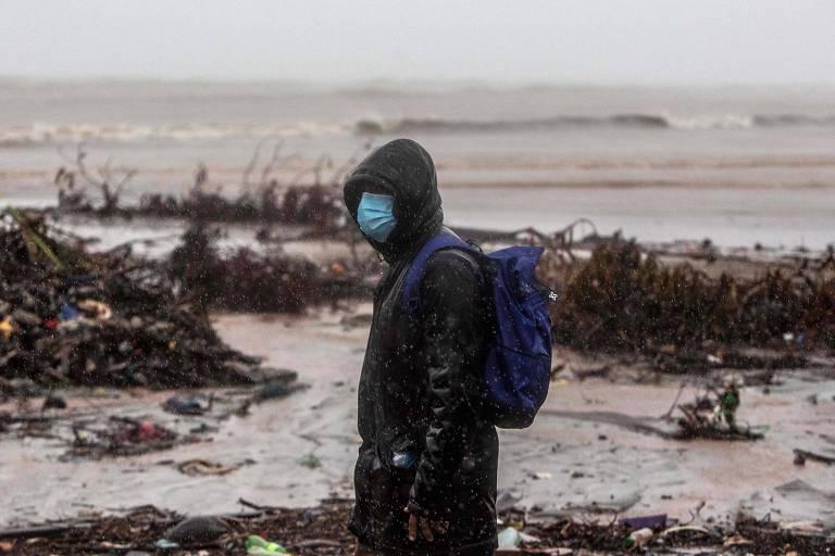 Homem usa máscara enquanto anda por praia no bairro de Bilwi, na cidade de Puerto Cabezas, uma das mais atingidas pela passagem do Iota na Nicarágua