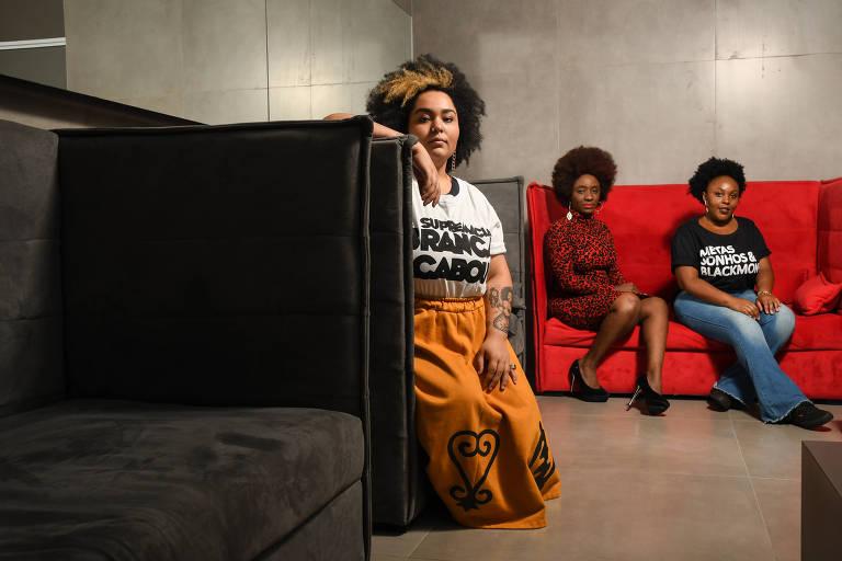 Três mulheres sentadas em um sofá