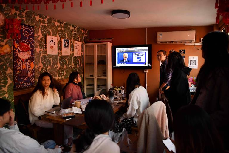 Jovens chineses que estudam em universidades americanas assistem à apuração das eleições presidenciais dos EUA, em Pequim