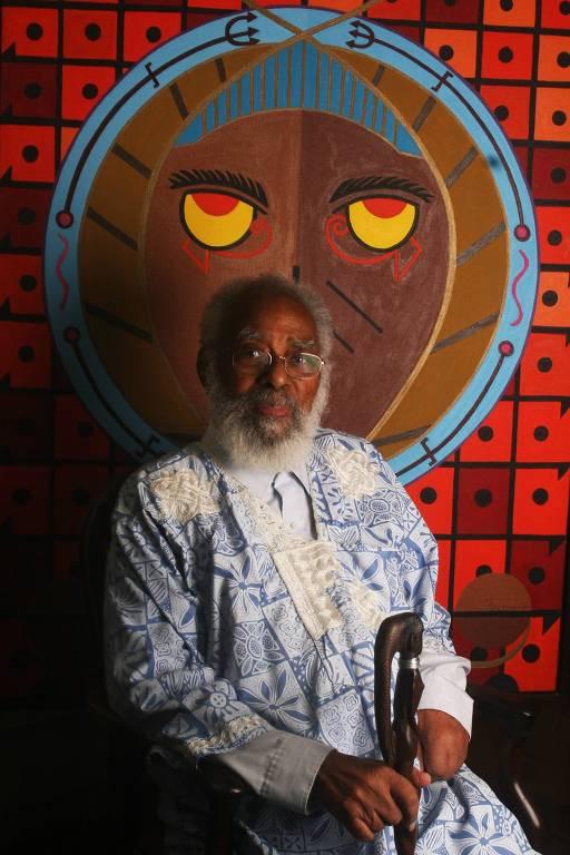 homem negro idoso veste traje com estampa azul clara e branca. ele está sentado diante de uma de suas obras, um painel vermelho vibrante. suas duas mãos repousam em uma elegante bengala de madeira. ele olha para a câmera sem sorrir.