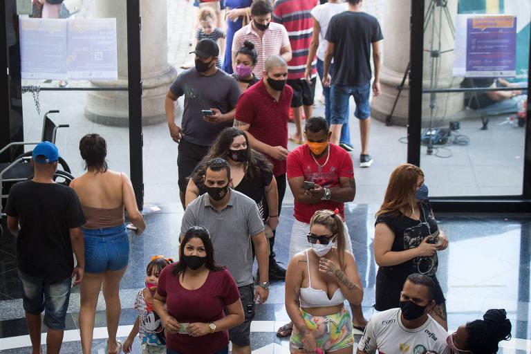 Pessoas em fila aguardam para votar. A fila é de duas em duas pessoas e está no centro da foto, ocupando do centro inferior ao superior da imagem