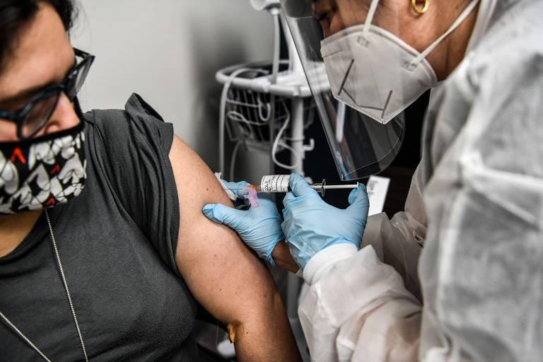 Mulher branca de camiseta preta, óculos e máscara estampada recebe vacina de enfermeira paramentada com máscara, luvas e EPI