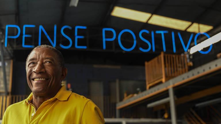 No canto direito, Geraldo Rufino usa uma camisa polo amarela e olha para o horizonte; acima de sua cabeça está um letreiro com a frase 'pense positivo'