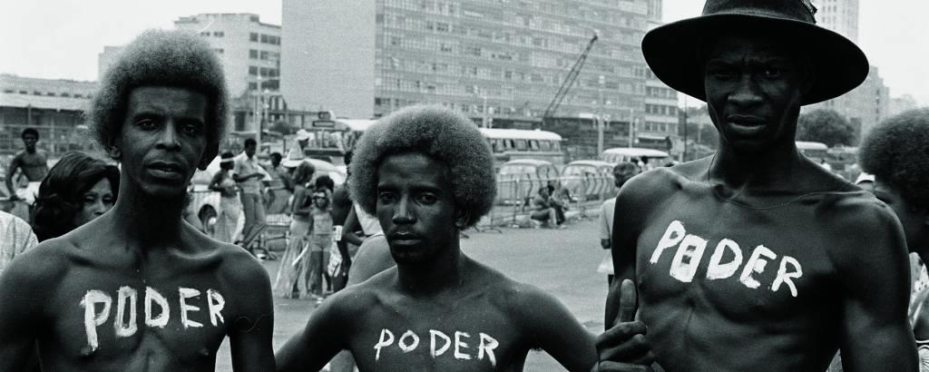 Imagem em preto e branco e em primeiro plano mostra três homens negros com