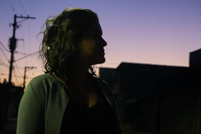 Foto mostra mulher de perfil, quase contra a luz do amanhecer, em tons de roxo e laranja, e a silhueta de casas e postes recortada entre ela e o céu