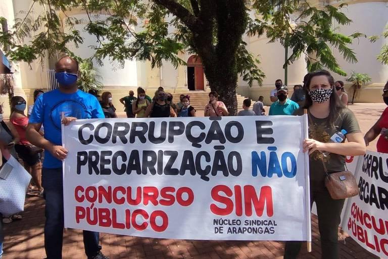 """Grupo de professores ao fundo com dois à frente segurando faixa com a inscrição: """"corrupção e precarização, não; concurso público, sim"""""""