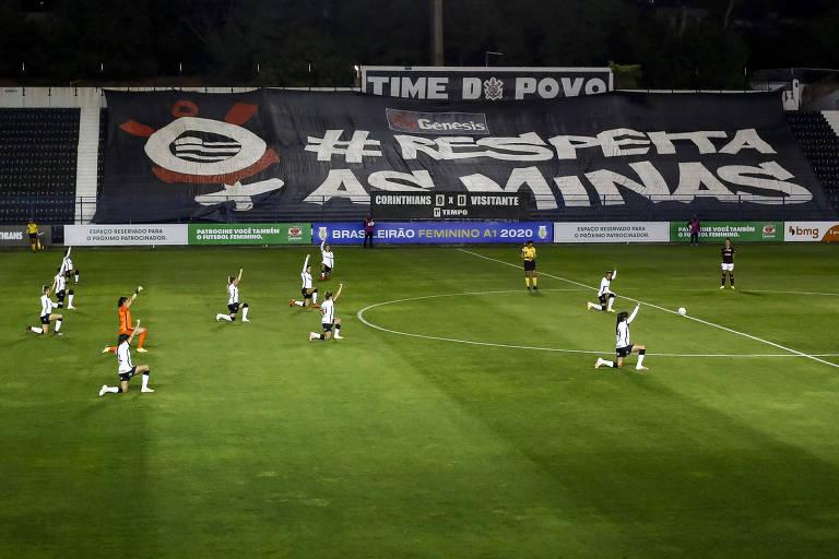 """Jogadoras do Corinthians com um dos joelhos no chão, o punho erguido; na arquibancada, uma faixa """"respeita as minas"""""""