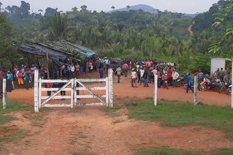 Grupo de pessoas aglomeradas após uma cerca, próximos a uma espécie de barracão feito com lona preta; na direita da foto, é possível ver também motos