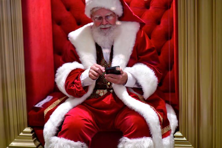 Papai Noel usa celular enquanto espera visitas em shopping nos EUA