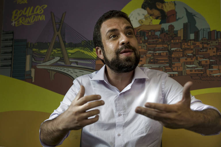 O candidato Guilherme Boulos, do PSOL, está de camisa branca com o antebraço de fora e barba. Ele gesticula com as duas mãos. Ao fundo, um desenho com cores amareladas