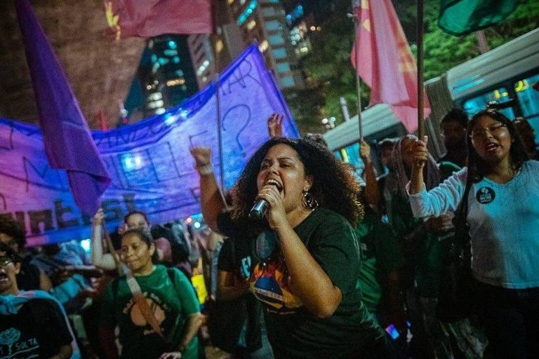 Rozana, mulher negra, discursa em protesto cercada por mulheres que empunham bandeiras